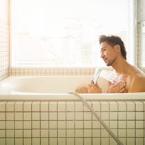 Asian man showering in modern Japanese bathtub, back lit by window.