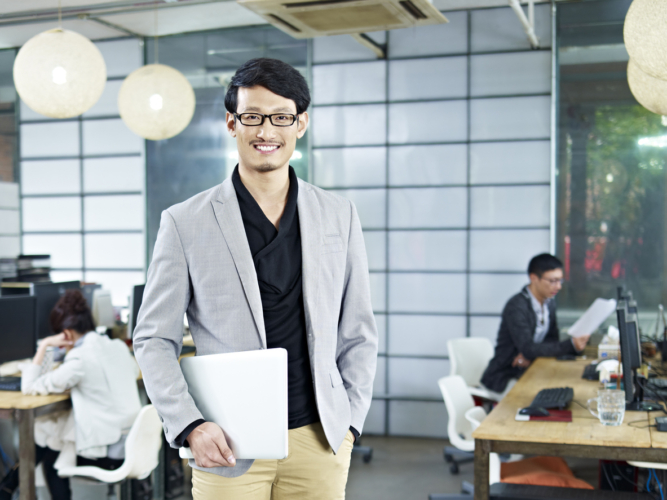 young asian entrepreneur standing in office with laptop computer under arm.