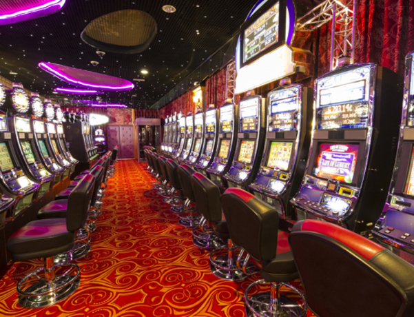 A lot of Slot machines in an empty  Casino.