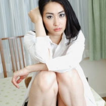 Beautiful Japanese girl sitting in a dining room.