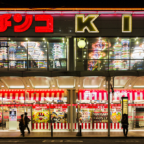 Kyoto, Japan - October 21, 2012: People walking in front of Pachinko parlor in Kyoto Japan. Many amusement parks like the one in the picture contain Pachinko slot machines very popular in Japan. This form of gambling is estimated to generate more than 300 billions anually.