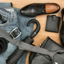 Classic black shoes and men's clothes and accessories lie on the wooden floor, can be used as background, top view