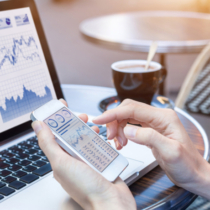 Close-up of hands of businesswoman analyzing stock market charts and key performance indicators (KPI) with business intelligence (BI) on notebook computer and smartphone screen, fintech (financial technology)