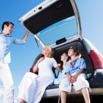 Happy family of four people sitting on a car trunk against the blue sky.