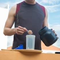 Whey protein, healthy lifestyle, man pour whey powder on the bottle.