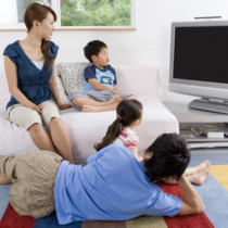 Family watching TV in living room