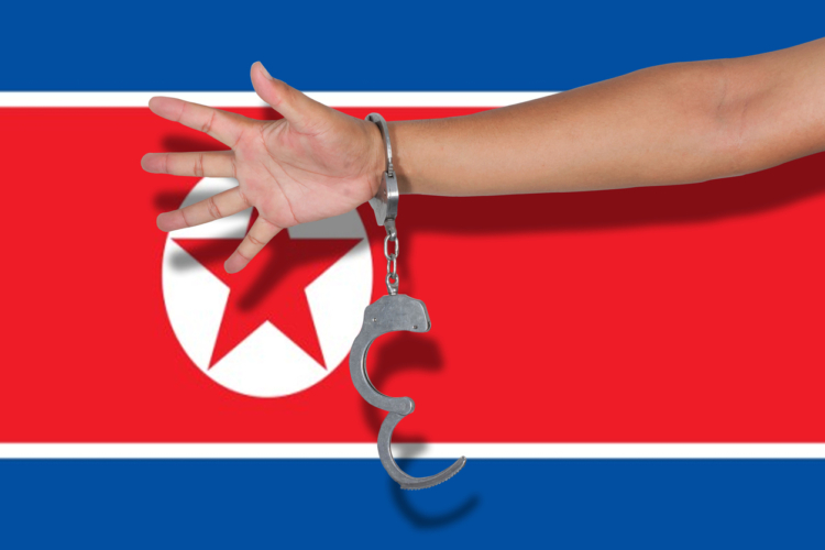 handcuffs with hand on North Korea flag