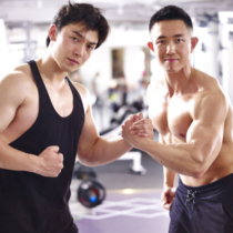portrait of two young asian bodybuilders posing in gym.