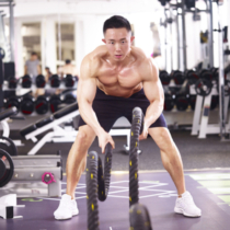 mid adult asian male bodybuilder working out in gym using battle ropes.