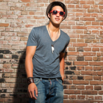 Urban asian man with red sunglasses. Good looking. Cool guy. Wearing grey shirt and hat and jeans. Standing in front of brick wall.