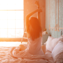Woman stretching in bed after wake up, back view. Model is posing in lingerie