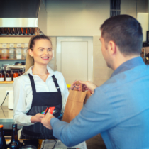 Man paying takeaway order by credit card on reader holded by smiling waitress working at shop counter restaurant. Customer using credit card for payment. Young cashier accepting payment over nfc technology